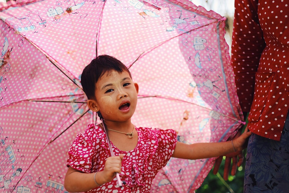 This girl lived on the same farm as the woman above, her face cooled with Thanakha and sheltered from the sun by her pink umbrella.