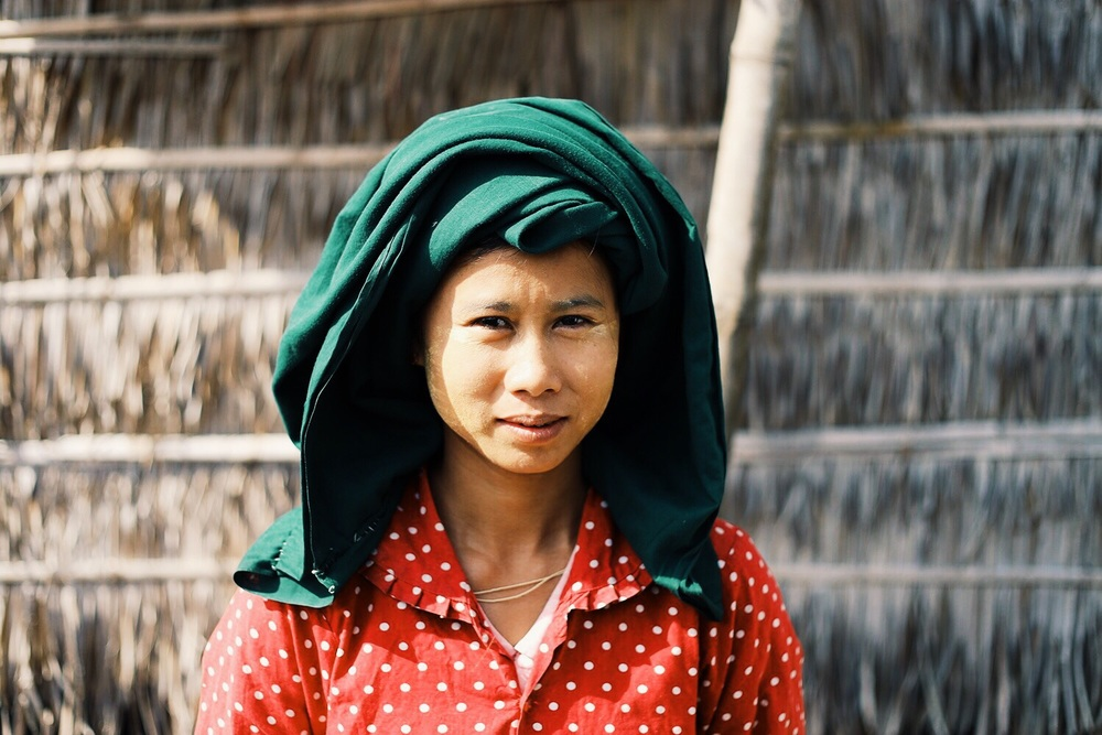 This woman, the mother of the girl with the pink umbrella in the second photo, cools her face with the cosmetic Thanaka paste that is popular throughout Myanmar.