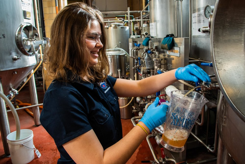 Elizabeth Curtis pulls a sample from a batch of beer mid-brew to test its consistency with other batches.