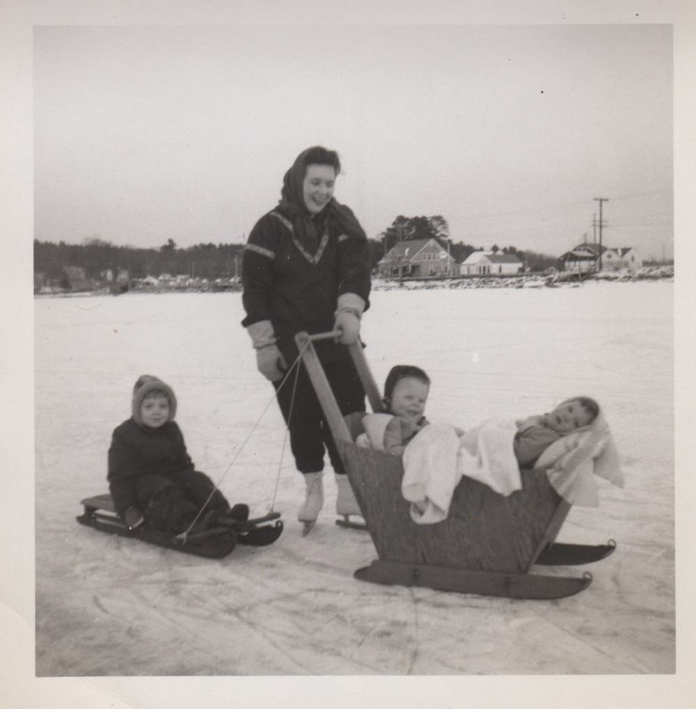December 1953, Long Lake in Naples, Maine.     My father made the plywood sleigh that my mother is pushing with my younger sister and I aboard. My older sister on the sled behind.  - James