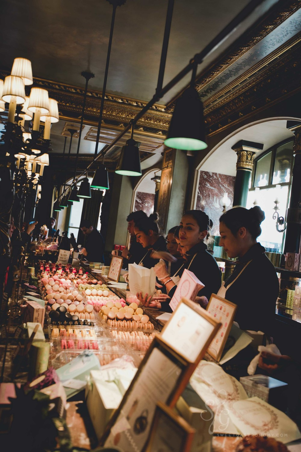 Hustling in the very busy  Ladurée  on Champs - Élysées to get our sweet treats.