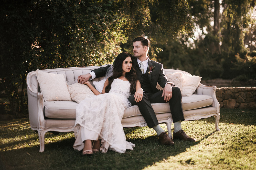 Bride and groom sit on a white vintage couch for a romantic wedding photo on the lawn of the Quail Haven Farm in Vista, California.