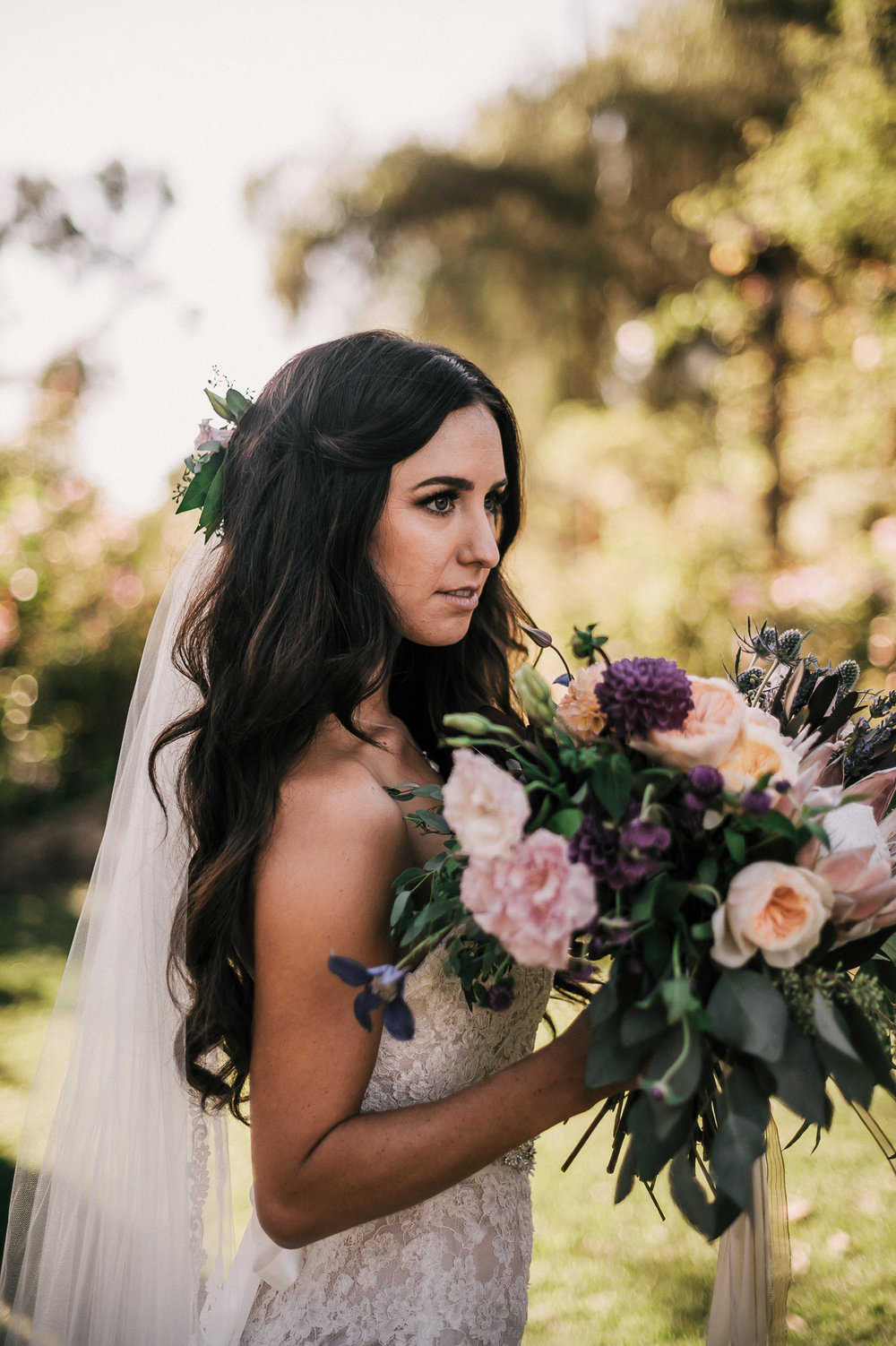 Bride shows off her beautiful bouquet with eucalyptus details in the golden light of sunset.