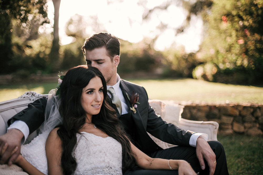 Groom loves on his new wife while they sit on a vintage couch at their Quail Haven Farm wedding.