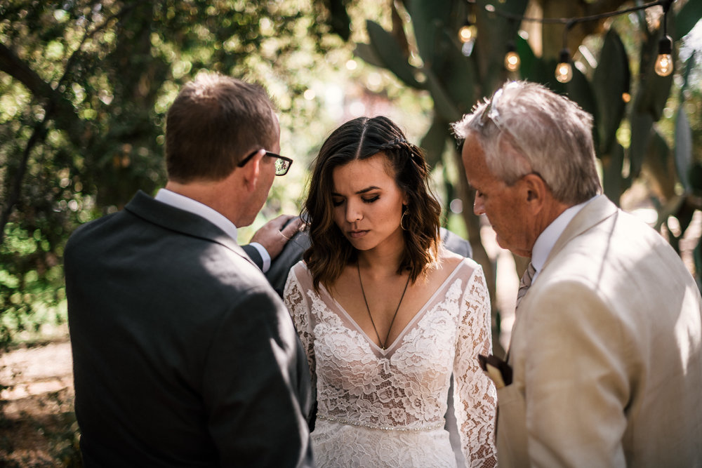 bride and groom's fathers pray for them at rustic Pymm ranch wedding venue in Winchester California