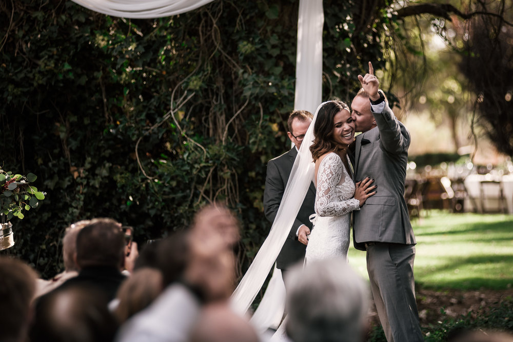 groom celebrates and kisses brides cheek at rustic pymm ranch wedding venue in winchester california