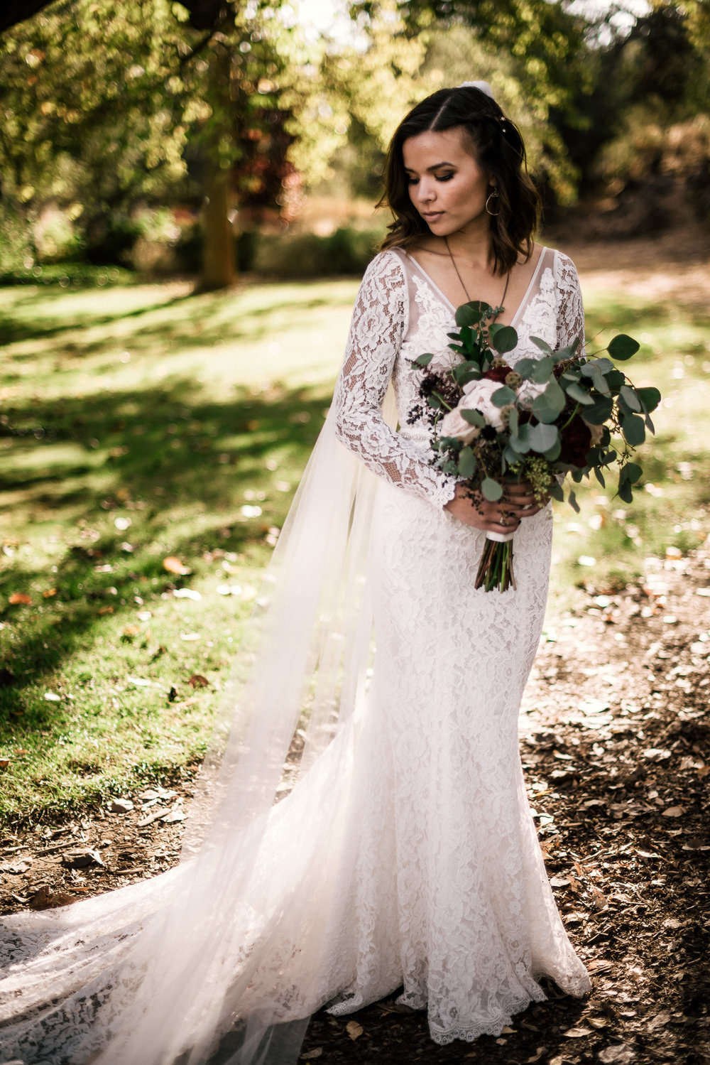 bride in lace dress and eucolyptus bouquet at rustic pymm ranch wedding venue in winchester california