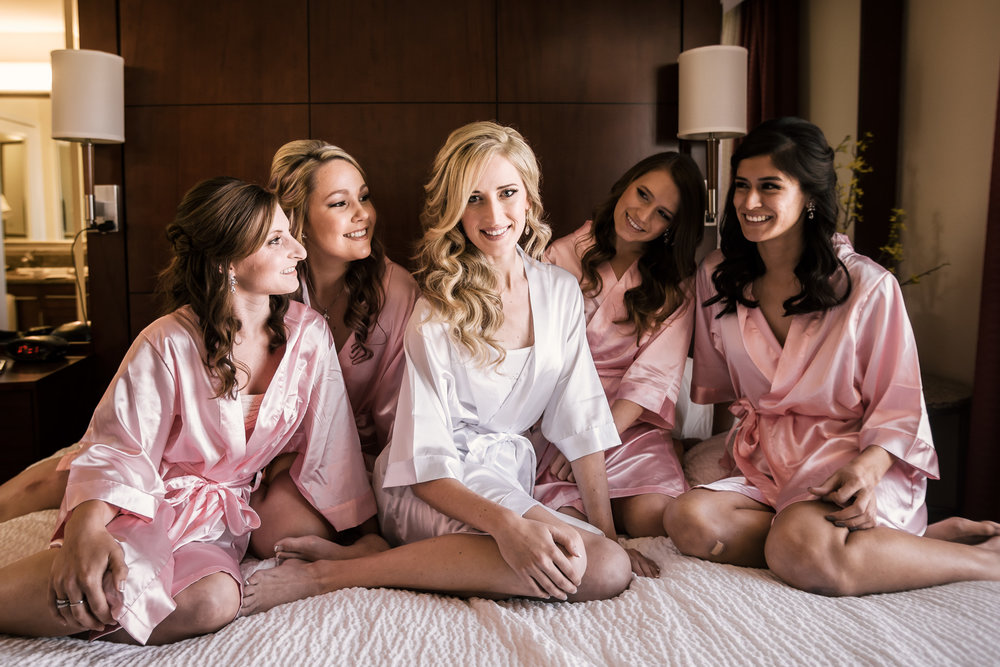 bride sits on a bed with her bridesmaids in their robes at the Twin Oaks Golf Course in San Marcos, San Diegos premier wedding venue