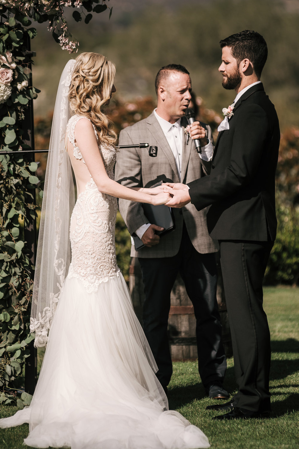 bride and groom hold hands during wedding ceremony at the Twin Oaks Golf Course in San Marcos, San Diegos premier wedding venue