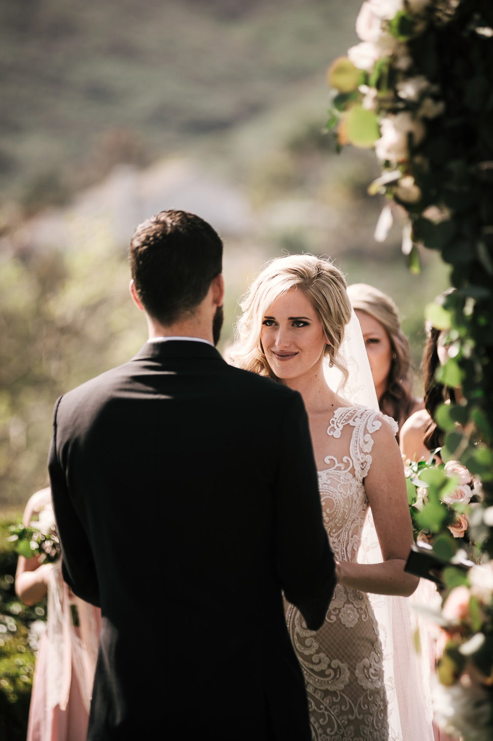 brides eyes full of emotion as she looks at groom saying his vows at the Twin Oaks Golf Course in San Marcos, San Diegos premier wedding venue