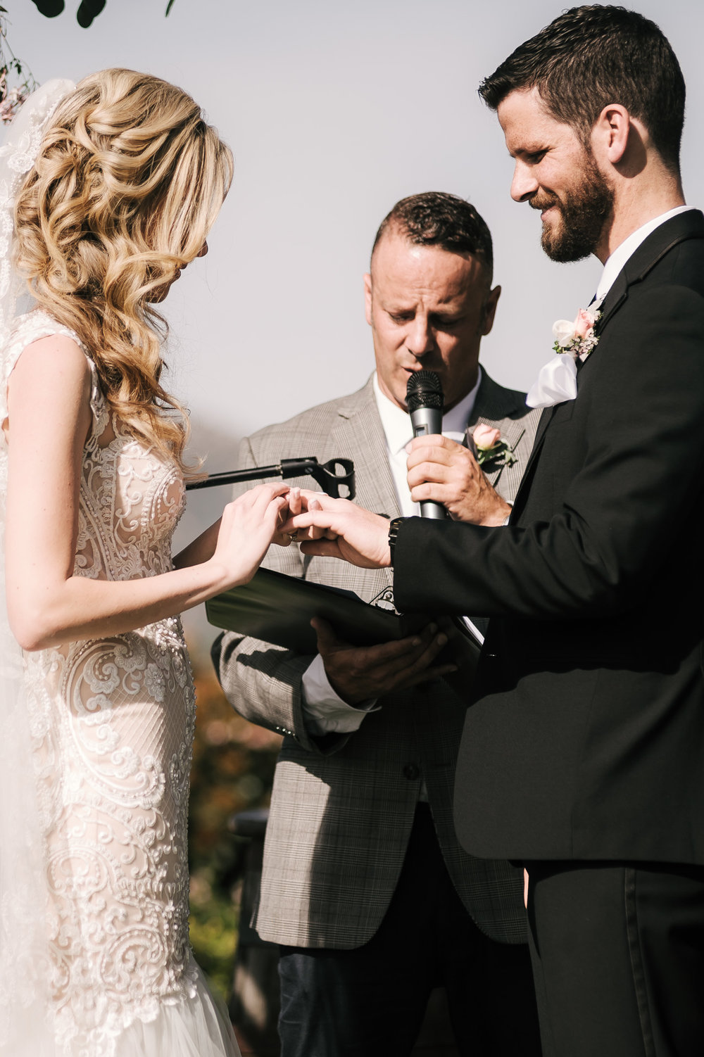 Bride palces ring on grooms finger at the Twin Oaks Golf Course in San Marcos, San Diegos premier wedding venue