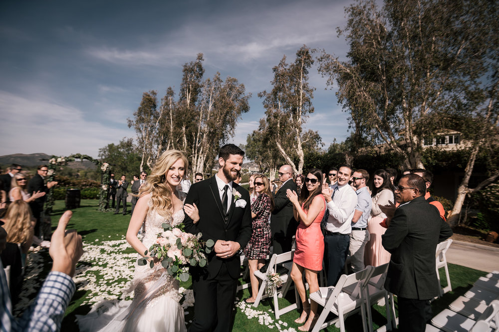 bride and groom get a thumbs up as they leave their ceremony at the Twin Oaks Golf Course in San Marcos, San Diegos premier wedding venue