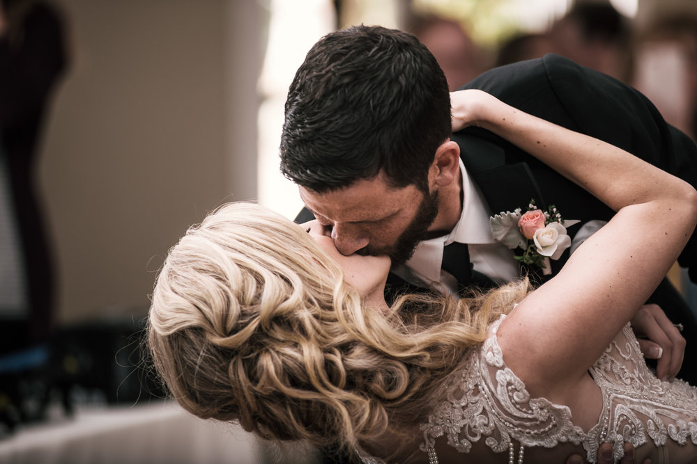 groom gives his bride a kiss while diping her at the Twin Oaks Golf Course in San Marcos, San Diegos premier wedding venue