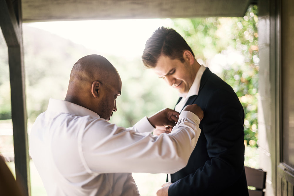 Best man fixes grooms handkerchief at the secret garden located at the Historic Parish ranch in Oak Glen California