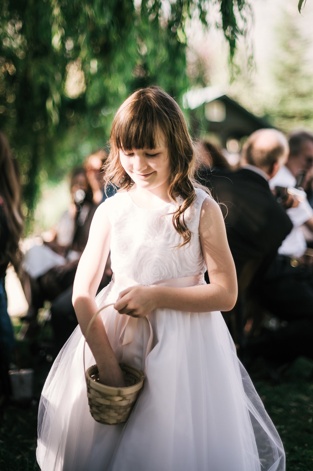 flower girl walks down the aisle at the secret garden located at the Historic Parish ranch in Oak Glen California