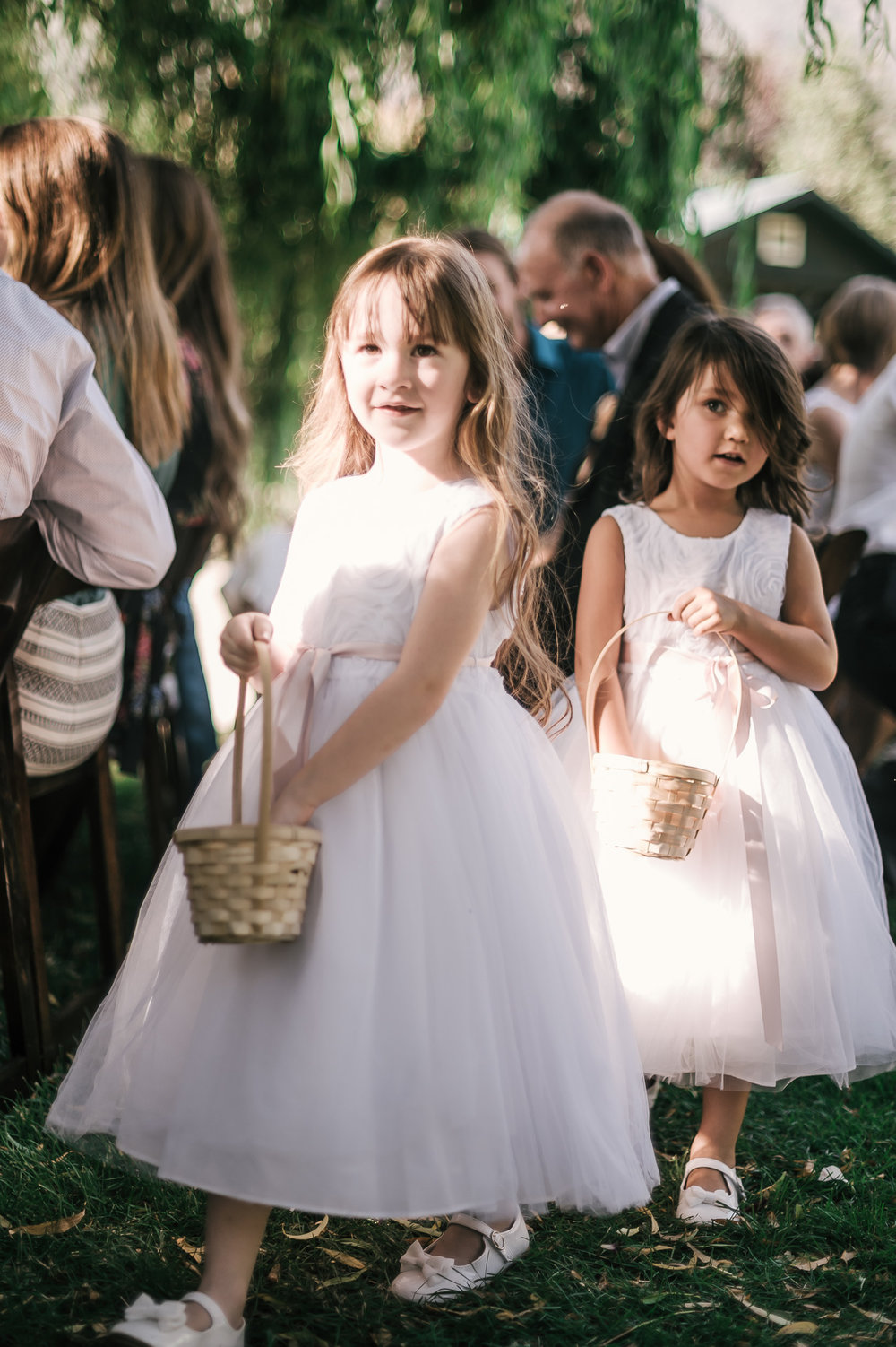 flower girls spread petals as they come down the aisle at the secret garden located at the Historic Parish ranch in Oak Glen California