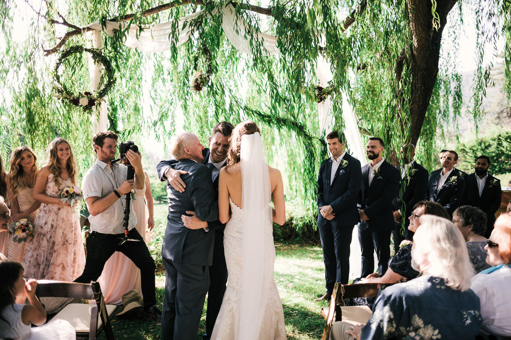 groom shares a laugh with the father of the bride as they hug at the secret garden located at the Historic Parish ranch in Oak Glen California