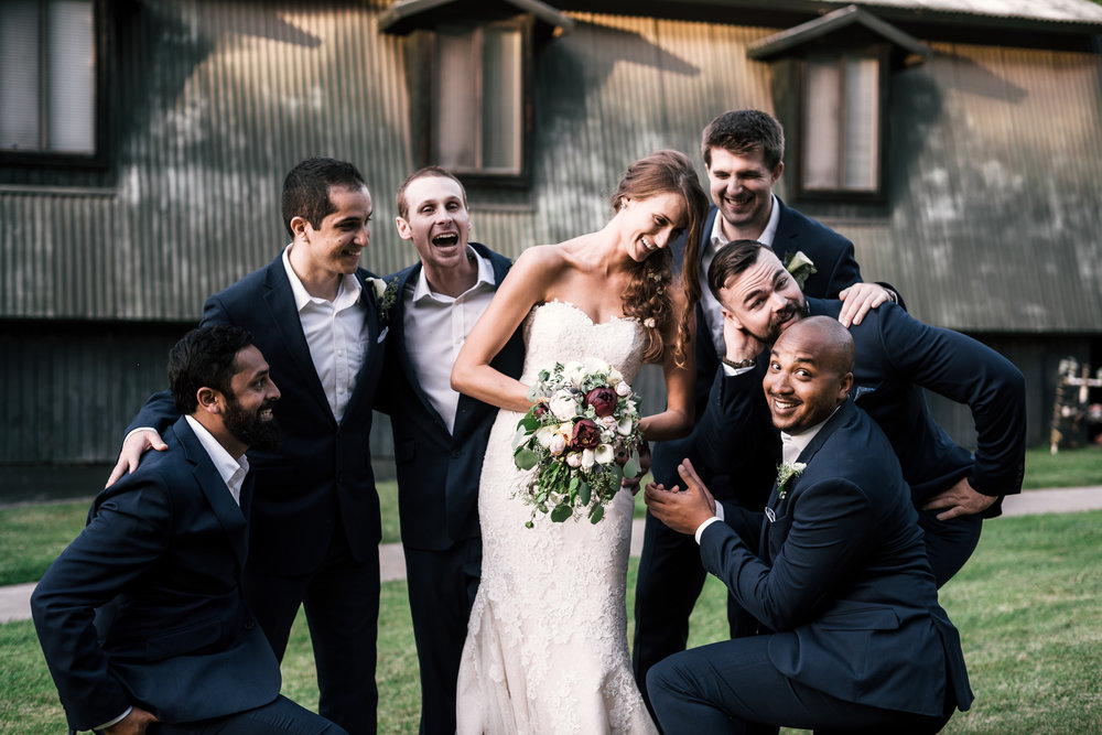 groomsmen goof off with the bride at the secret garden located at the Historic Parish ranch in Oak Glen California