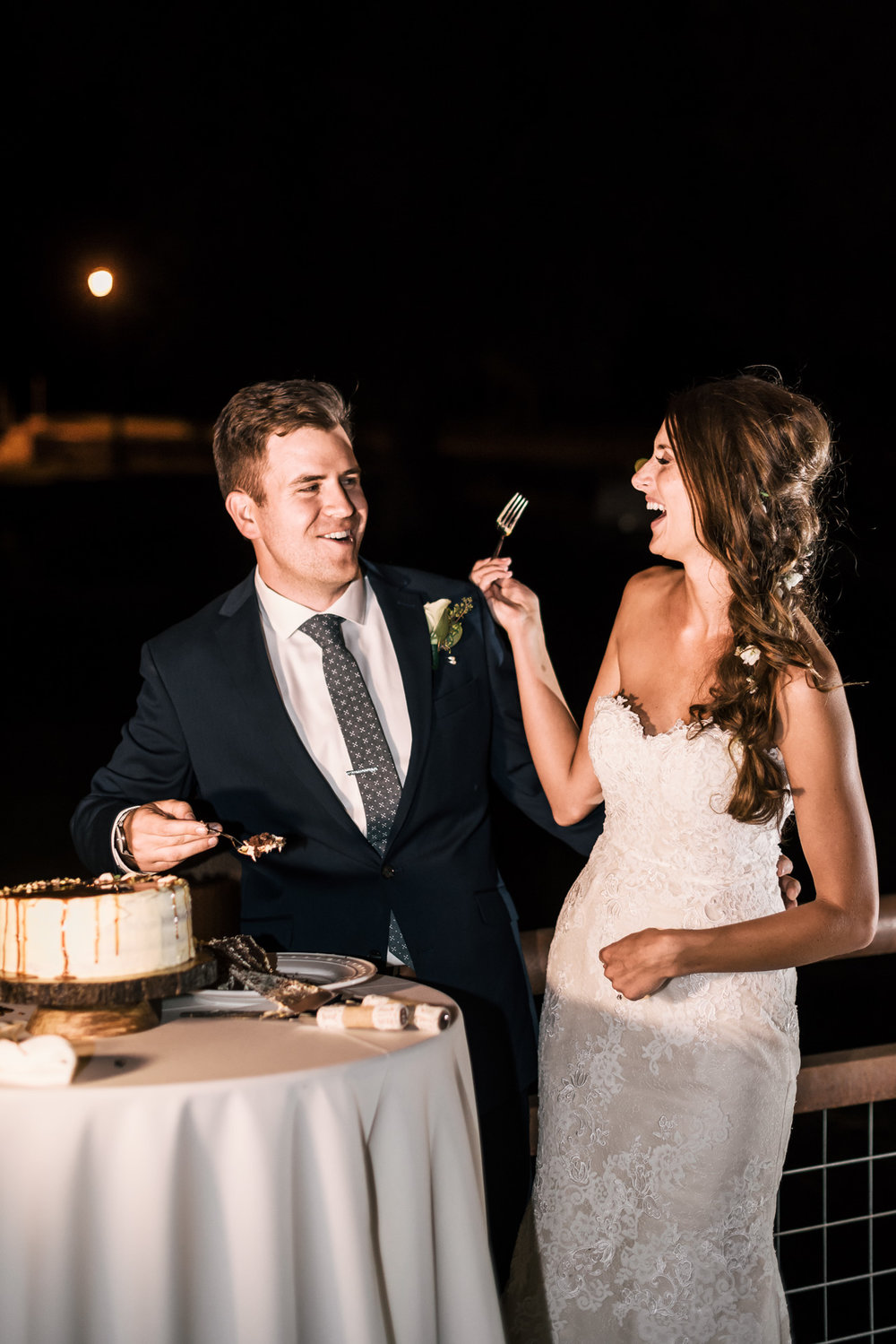 bride and groom share a laugh after cake cutting during their wedding at the secret garden located at the Historic Parish ranch in Oak Glen California