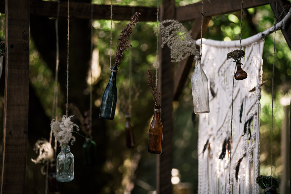 hanging colored glass bottles with rustic plants shot by wedding photographer at the charming St. George Hotel in Volcano California