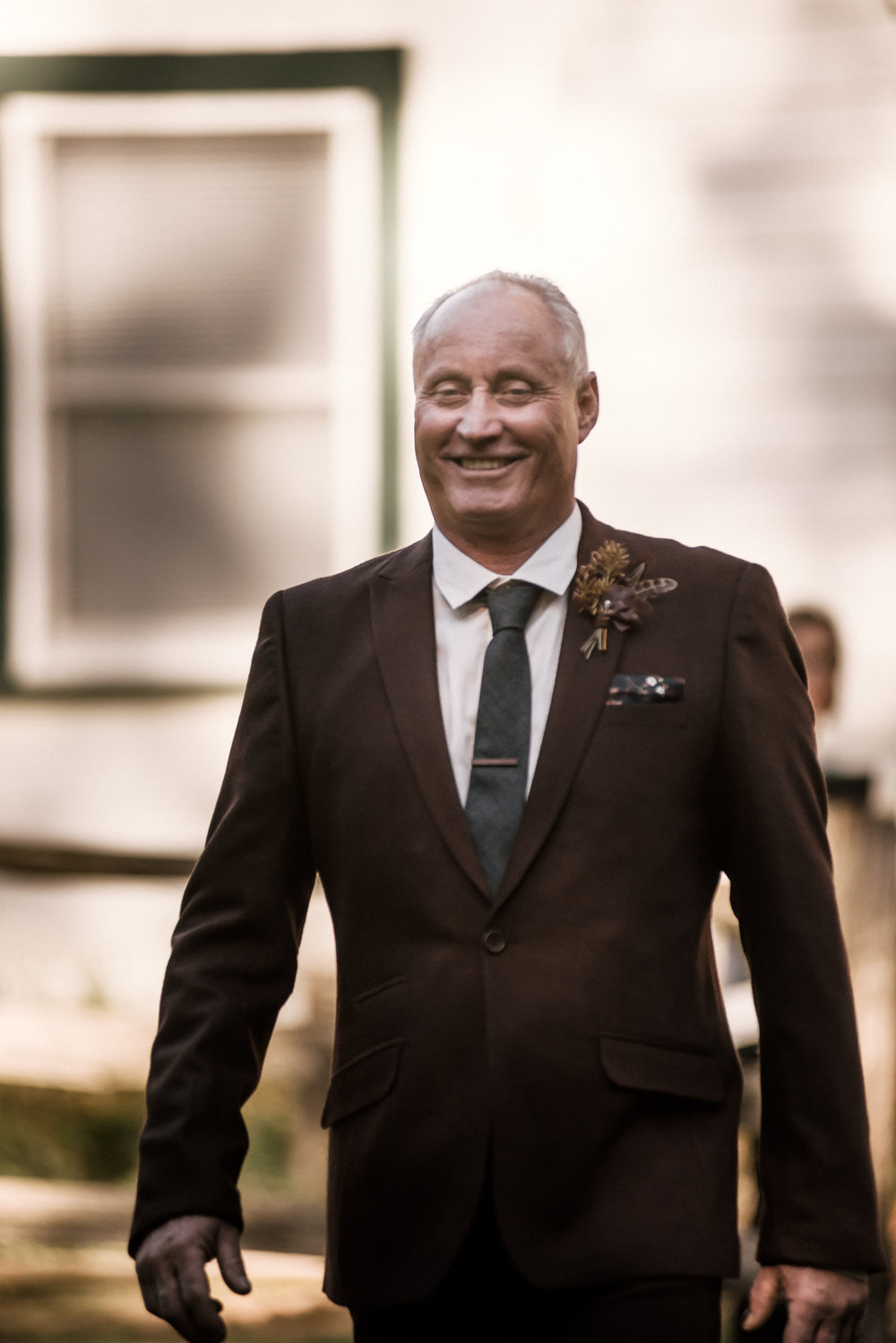 father of the groom goes down the aisle with a smile shot by wedding photographer at the charming St. George Hotel in Volcano California