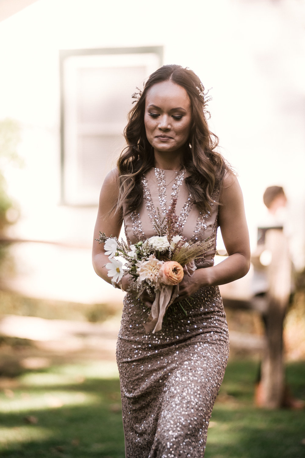 bridesmaid walks down the aisle with her bouquet shot by wedding photographer at the charming St. George Hotel in Volcano California
