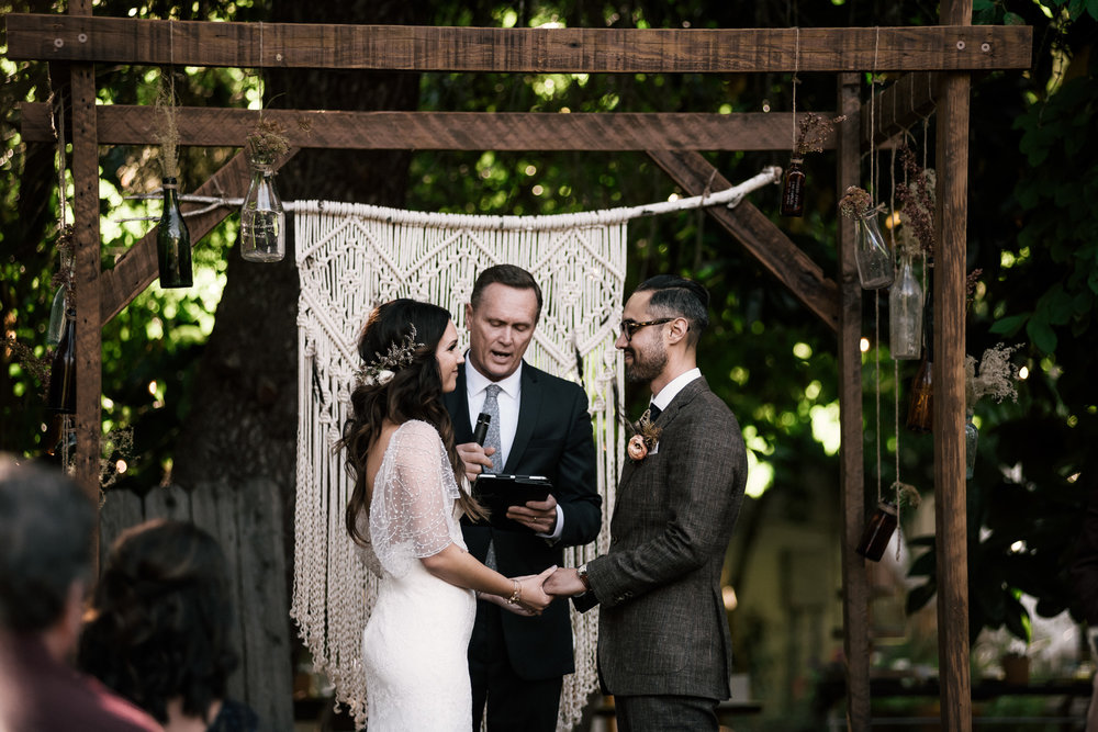 couple looks deep into eachothers eyes as the pastor perfroms ceremony shot by wedding photographer at the charming St. George Hotel in Volcano California