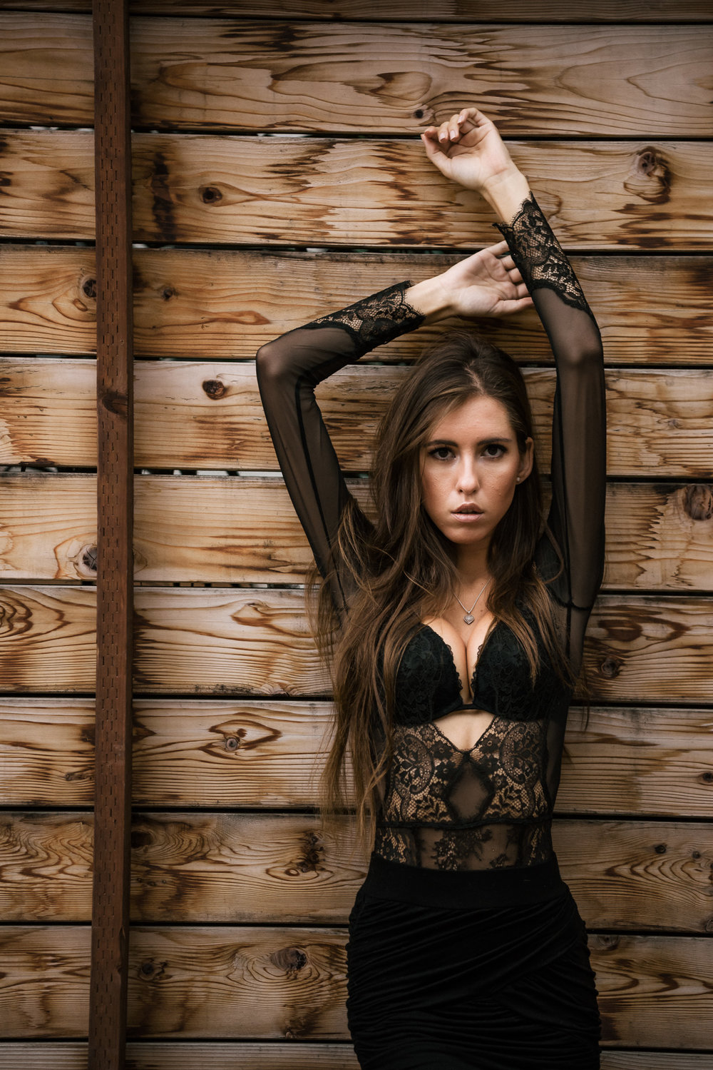 Model poses against a wooden wall for urban style shoot at The Hungarion Brunette Lingerie as outerwear fashion photoshoot in Venice Beach California