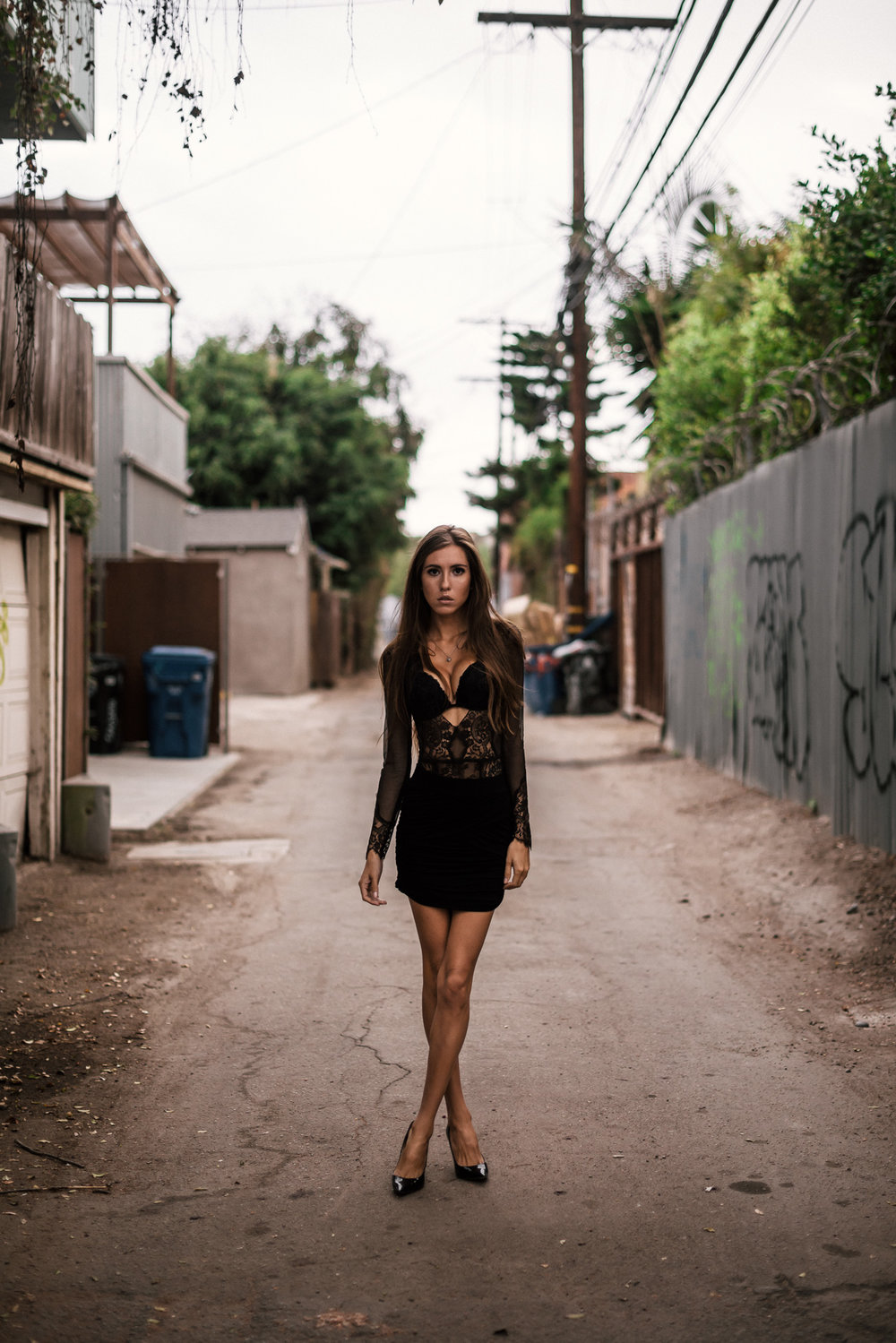 model poses in city alley The Hungarion Brunette Lingerie as outerwear fashion photoshoot in Venice Beach California