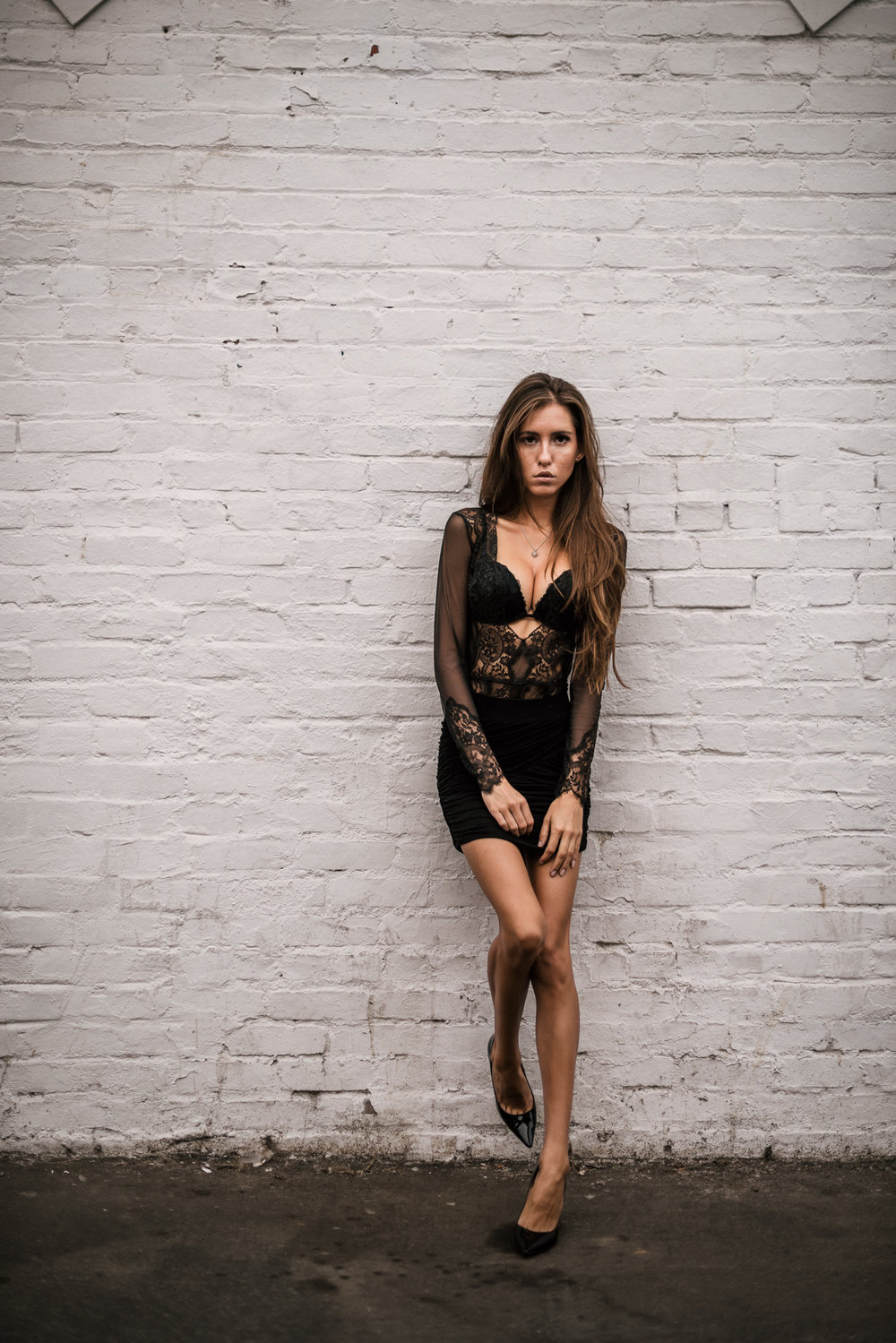 woman gazes into camera leaned against white wall standing on one leg at The Hungarion Brunette Lingerie as outerwear fashion photoshoot in Venice Beach California