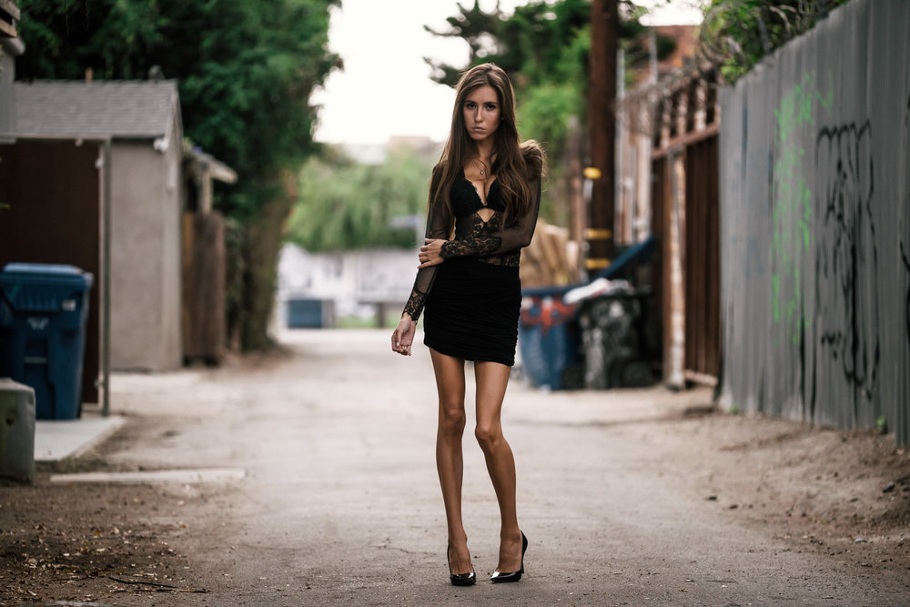 model poses in the middle of an alley at The Hungarion Brunette Lingerie as outerwear fashion photoshoot in Venice Beach California