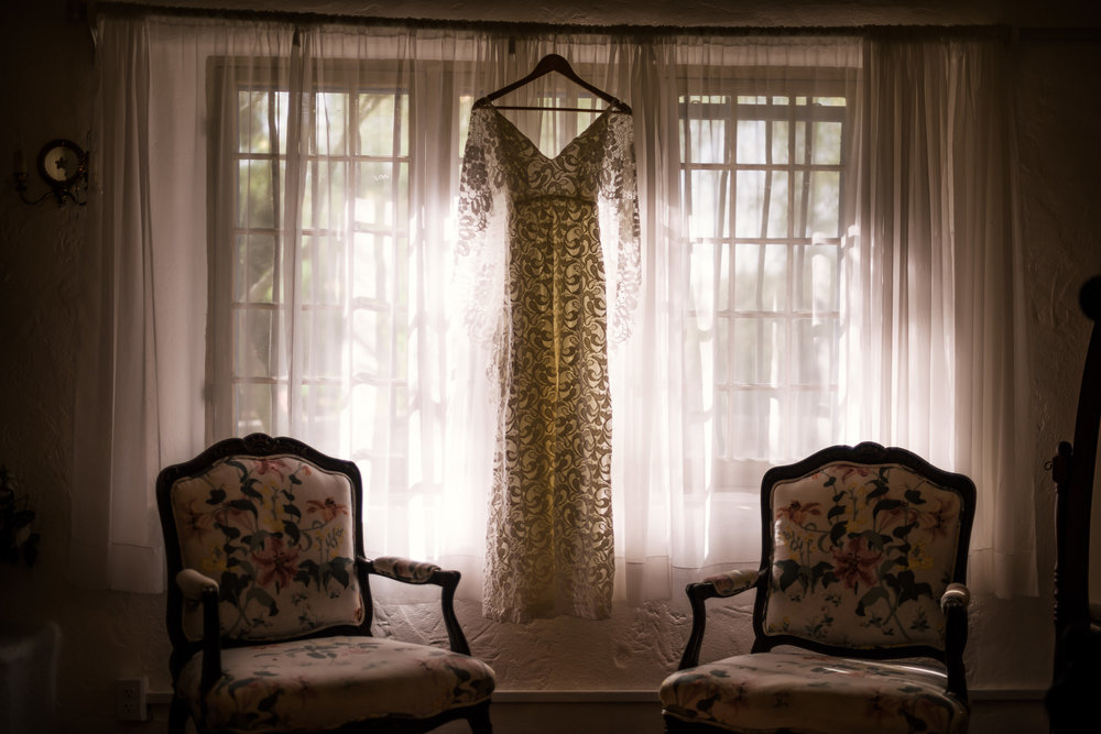 Brides wedding dress hangs backlit by window light between two chairs captured by photographer during romantic wedding at the historic Leo Carrillo Ranch in Carlsbad California
