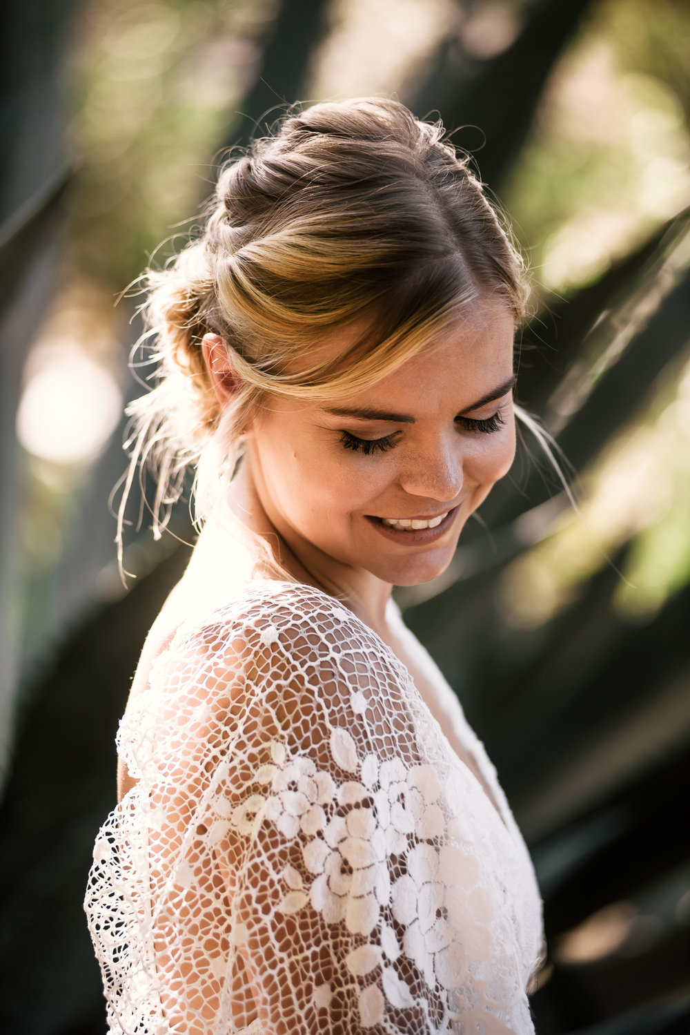 bashful bride poses for a portrait captured by photographer during romantic wedding at the historic Leo Carrillo Ranch in Carlsbad California