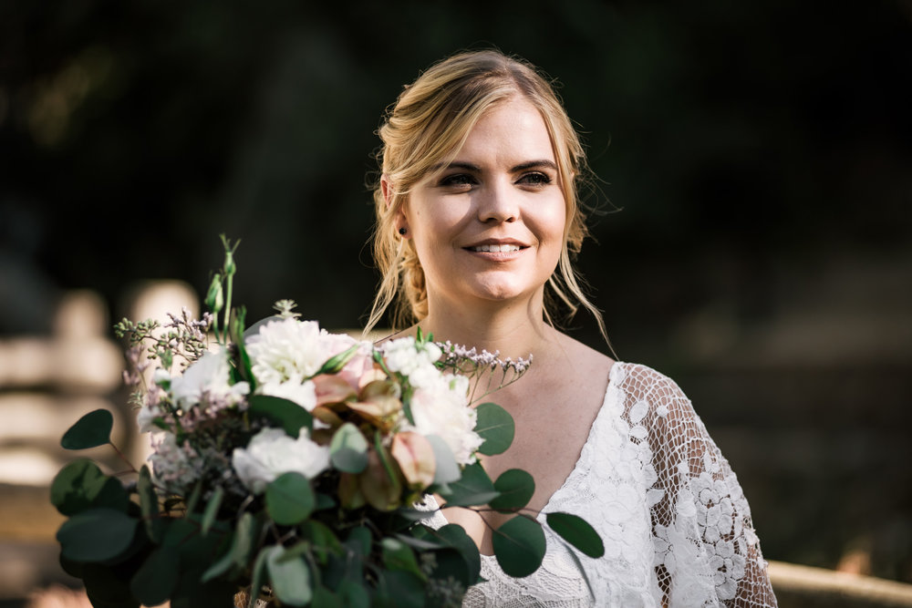 bride smiles with her bouquet captured by photographer during romantic wedding at the historic Leo Carrillo Ranch in Carlsbad California