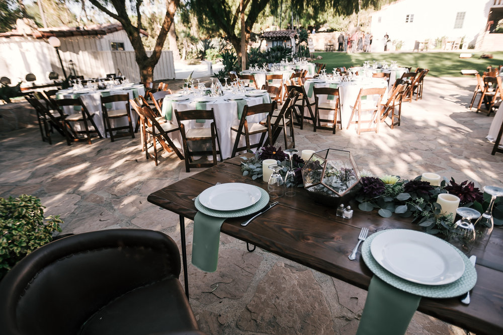 head table with flower details with guest tables in the background captured by photographer during romantic wedding at the historic Leo Carrillo Ranch in Carlsbad California