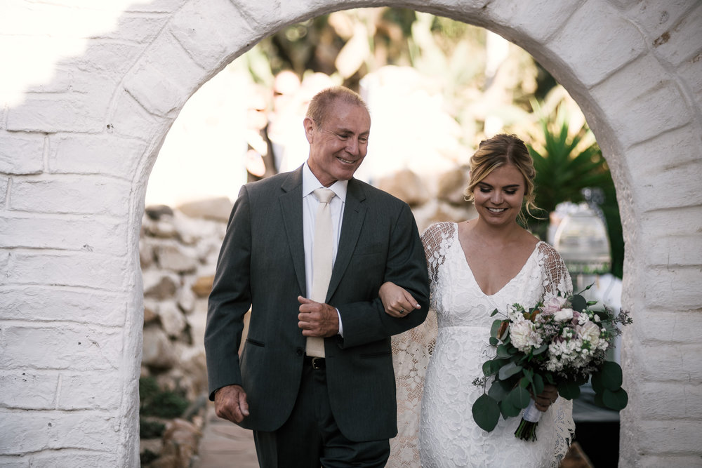Father walks his daughter down the aisle captured by photographer during romantic wedding at the historic Leo Carrillo Ranch in Carlsbad California