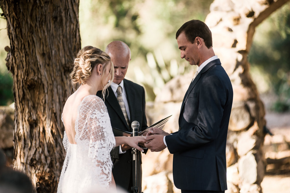 groom puts ring on brides finger captured by photographer during romantic wedding at the historic Leo Carrillo Ranch in Carlsbad California