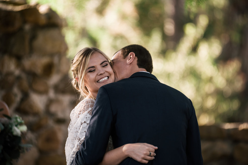 groom whipsers sweet words into brides ear after first kiss captured by photographer during romantic wedding at the historic Leo Carrillo Ranch in Carlsbad California