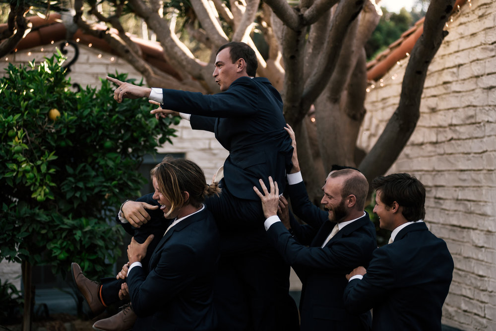 groomsmen carry groom after the ceremony captured by photographer during romantic wedding at the historic Leo Carrillo Ranch in Carlsbad California