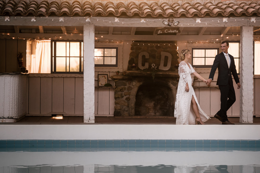 couple goes on a romantic walk captured by photographer during romantic wedding at the historic Leo Carrillo Ranch in Carlsbad California