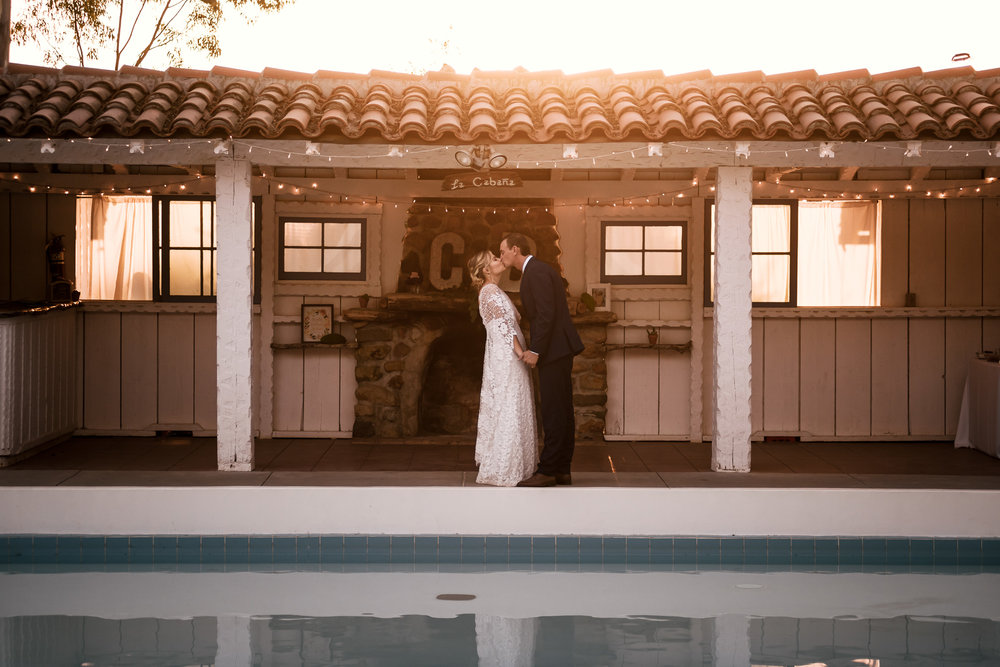 couple has romantic kiss by the pool at sunset captured by photographer during romantic wedding at the historic Leo Carrillo Ranch in Carlsbad California