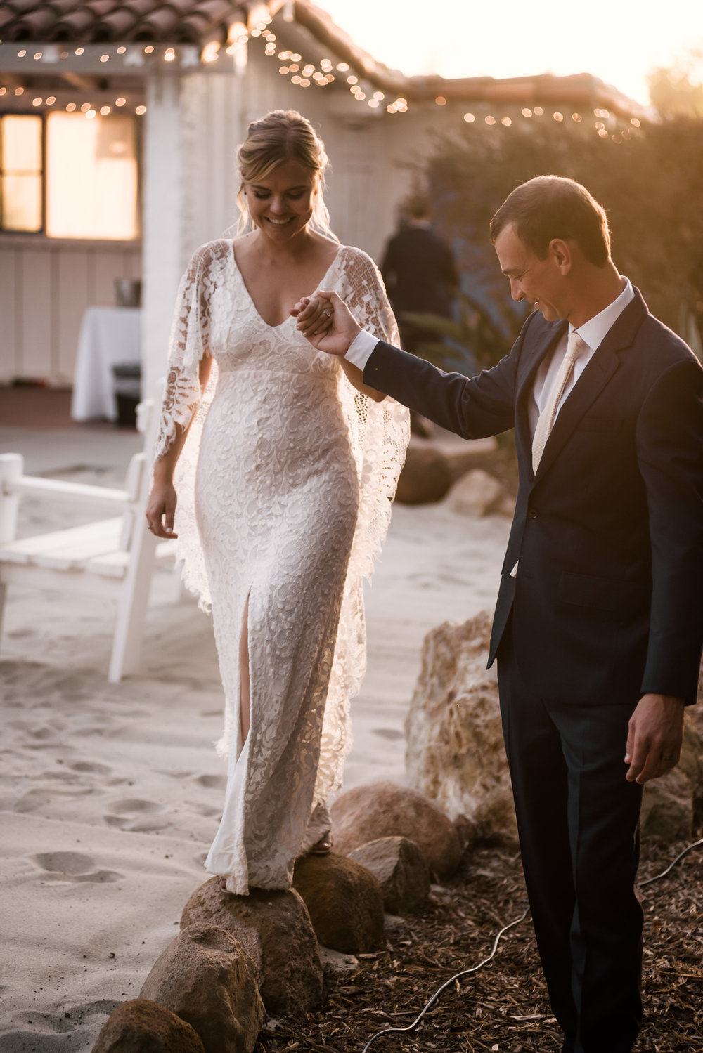 groom helps bride walk along the stones captured by photographer during romantic wedding at the historic Leo Carrillo Ranch in Carlsbad California