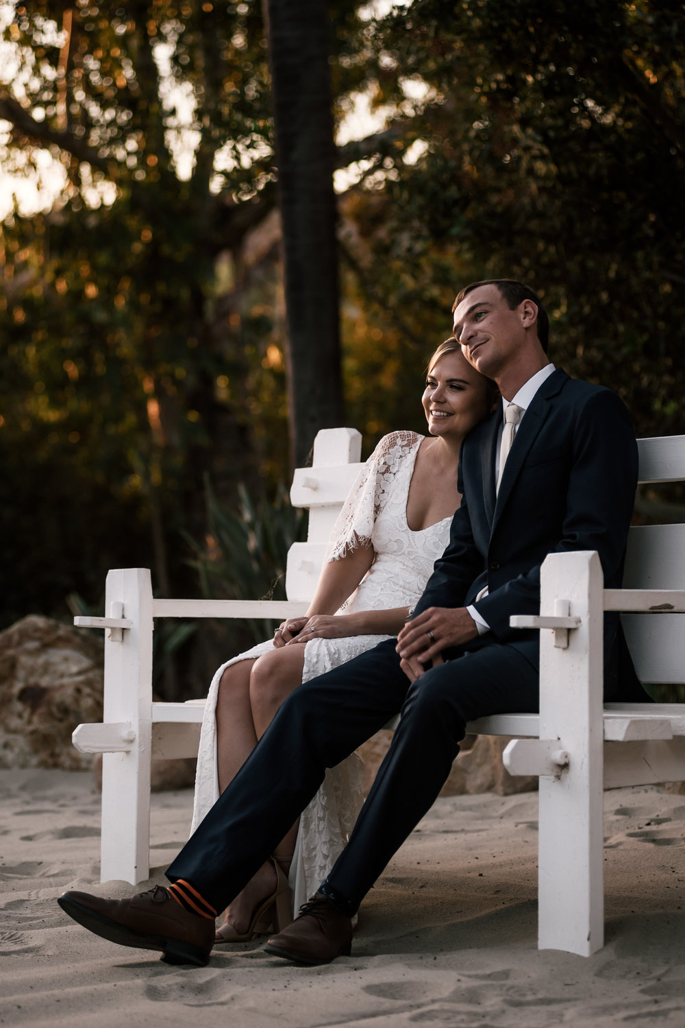 newly weds sit on a bench in the sand and enjoy the sunset captured by photographer during romantic wedding at the historic Leo Carrillo Ranch in Carlsbad California