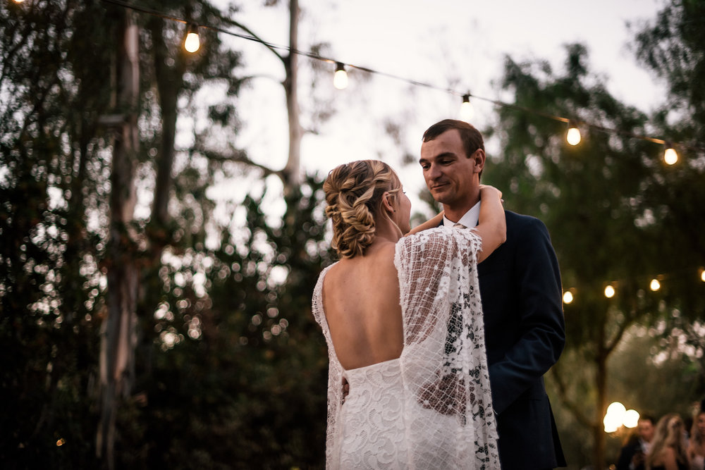 romantic dancing at sunset under hanging lights captured by photographer during romantic wedding at the historic Leo Carrillo Ranch in Carlsbad California