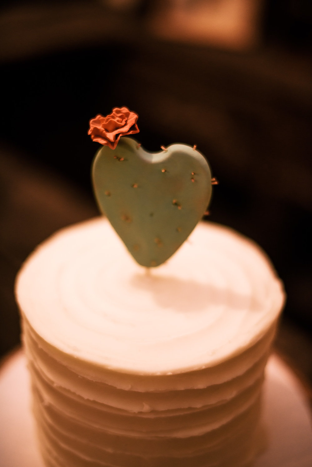 tiny red flower on heart shaped cactus topper captured by photographer during romantic wedding at the historic Leo Carrillo Ranch in Carlsbad California