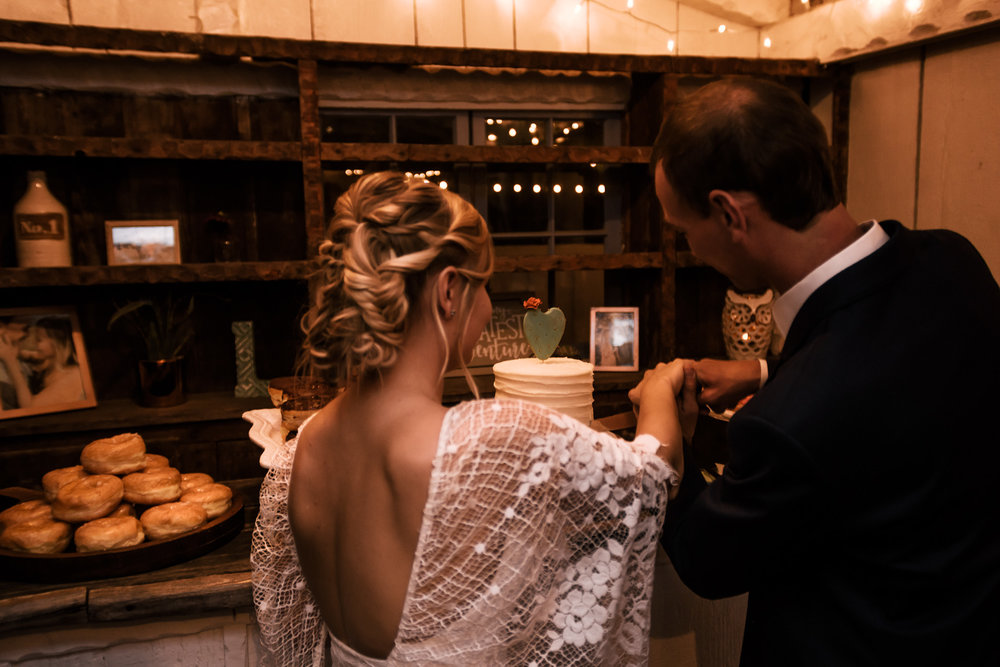 bride and groom cut the wedding cake captured by photographer during romantic wedding at the historic Leo Carrillo Ranch in Carlsbad California