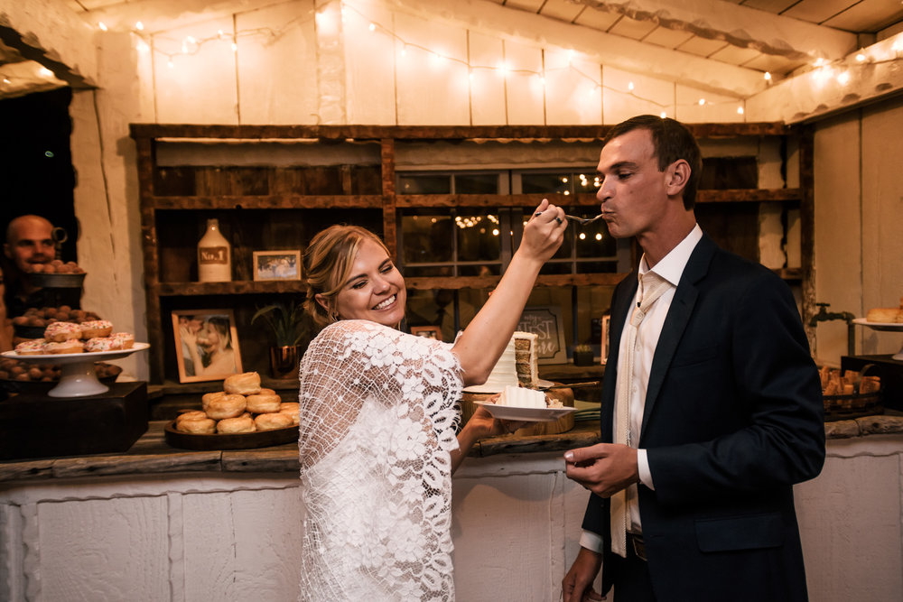 bride gives her husband a bite of cake captured by photographer during romantic wedding at the historic Leo Carrillo Ranch in Carlsbad California