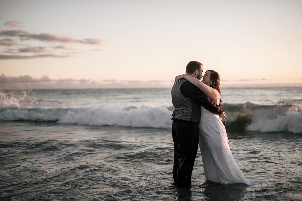 Couple stands in the ocean as waves crash around them at sunset after their wedding at Laguna Beach