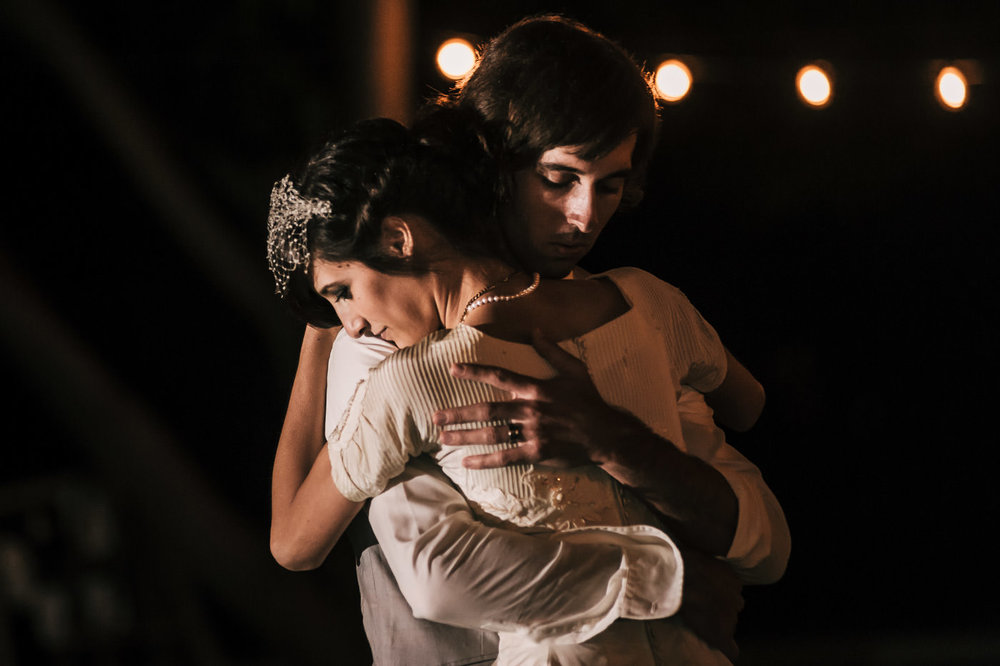 Couple enjoys a romantic slow dance and hold each other tightly after their vintage themed wedding in Temecula California