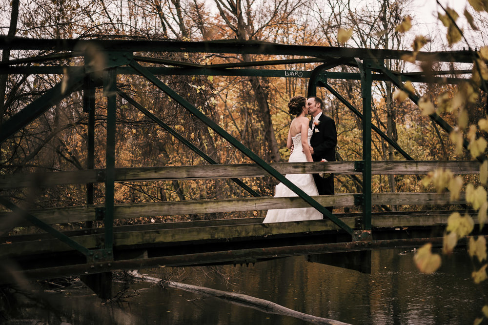 Bride and groom have a romantic kiss on an old wood and steel bridge over a river among the stunning colors of fall in Michigan